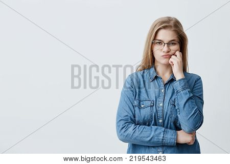 Headshot of caucasian blonde pretty female in denim shirt wearing glasses pouting her lips in dissatisfaction while doubting. Thoughtful girl crossing arms looks with disappointment and offense at camera poster