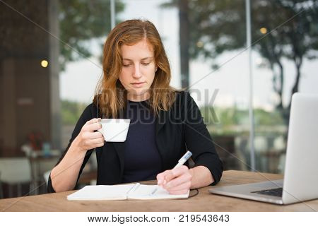 Portrait of focused young woman sitting at table with laptop, drinking coffee and writing in notebook. Student preparing for test. Work balance and education concept
