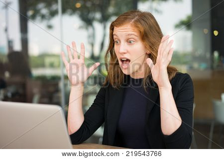 Portrait of surprised young woman looking at laptop screen with hands up gesture. She getting unexpected news during her break at outdoor office cafe. Good or bad news concept
