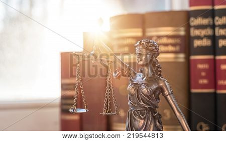The Statue of Justice - lady justice or Iustitia / Justitia the Roman goddess of Justice with sunlight and books in the background. ideal for websites and magazines layouts
