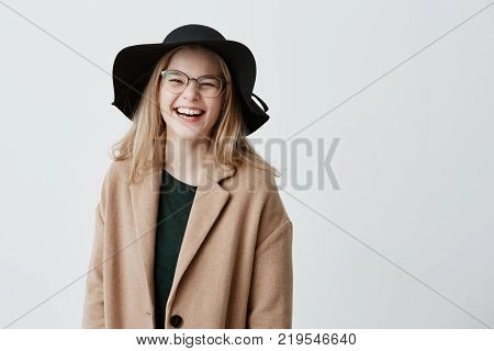 Beautiful euphoric teenage girl wearing stylish eyeglasses, black hat and coat, enjoying her life, looking and smiling at camera, full of joy and happiness. People and lifestyle concept