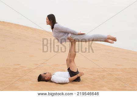 An Indonesian girl and Filipino boy doing a front bird yoga exercises on Dune 7, the highest sand dune in the world, in Walvis Bay, Namibia