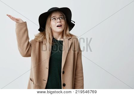Good-looking confused female gestures with puzzlement, tries to gather with thoughts, looks upwards isolated against gray background. Young woman has discontent expression wearing coat and hat