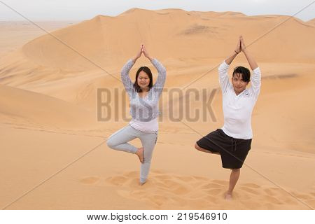 An Indonesian girl and Filipino boy doing a yoga tree on Dune 7, the highest sand dune in the world, in Walvis Bay, Namibia