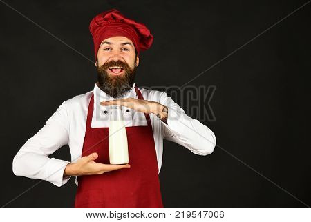 Cook With Excited Face In Burgundy Uniform Has Casserole
