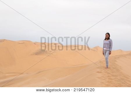 An Indonesian girl poses on Dune 7, the highest sand dune in the world, in Walvis Bay, Namibia