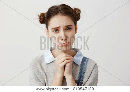 Close up portrait woman with brown hair in double buns pouting with pity look holding hands like praying. Pathetic expressions of girl asking for forgiveness over white wall. Concept of emotions Copy space.