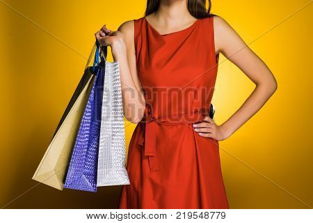 A girl in a beautiful red dress is holding packages with purchases in her hand
