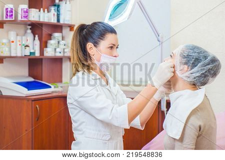 A girl at a doctor's appointment a cosmetologist a dermatologist a dentist or a plastic surgeon