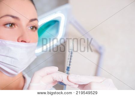 A nurse or doctor holding a syringe with a vaccine or medicine