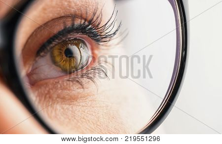 A close-up of Female eye that looks up with black glasses. ideal for websites and magazines layouts.