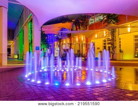 Grand Cayman, Cayman Islands, Dec 2017, illuminated fountain at night in a pedestrian zone