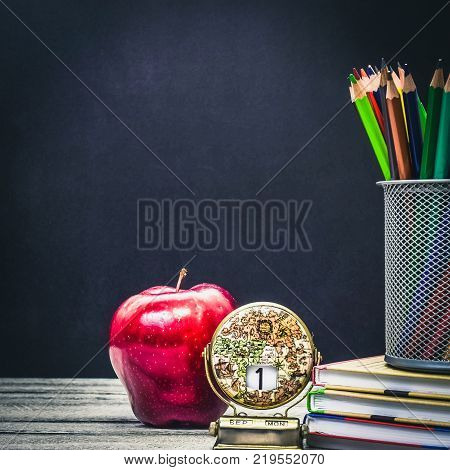 Back to School and Education concept. classroom with apple, books and pencils on chalkboard background. Calendar at the beginning of school school border with copy space