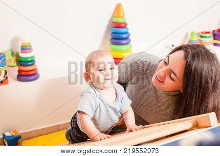 Young mother supports the baby, helping him climb the ladder in kindergarten
