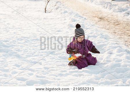 Boy playing with snowplow toy. Cold winter day