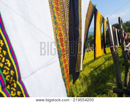 Colorful Thai sarongs fluttering in the wind on the rice field meadow Thailand