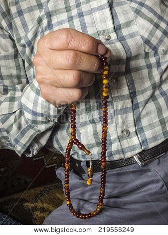 a Muslim man who attracts praise, a Muslim who worships a Muslim man pulling a rosary a Muslim woman who is attracting praise