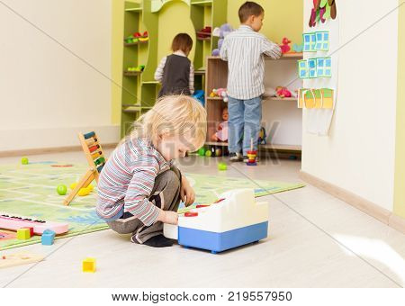 Boy is playing in the role of cashier  in the kindergarten