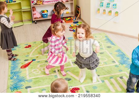Group of little children dancing and claping in hands