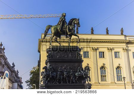 Bronze equestrian statue of King Frederick the Great. Blue sky and dark shapes. Berlin Germany .