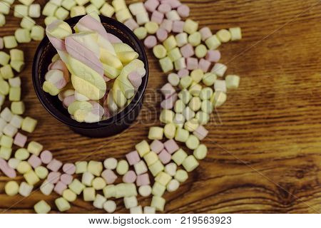 marshmallow Candies placed in a basket around the other candies. valentine's day and love concept on wooden background