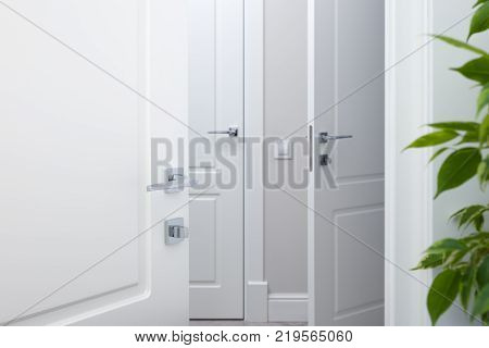Open the white door into the corridor. Chrome modern door handles