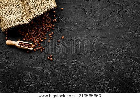 Fresh roasted coffee beans in scoop near canvas on black table top view.