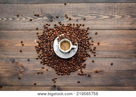 Cup of milky coffee on dark wooden table top view. Coffee background