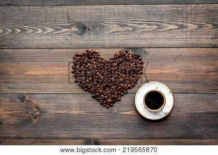 Cup of freshly brewed full-bodied coffee on dark wooden table top view copyspace. Coffee background