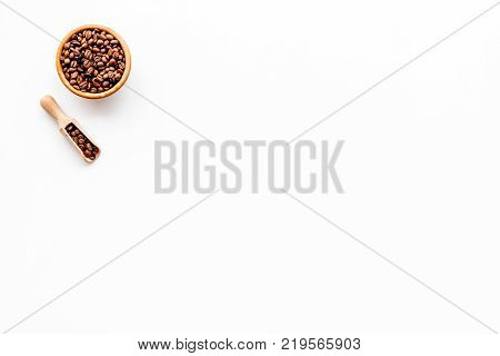 Fresh roasted coffee beans in bowl and scoop on white table top view copyspace. Coffee background