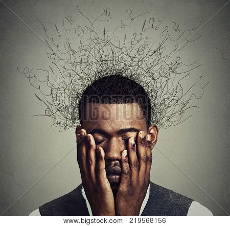 Depressed worried young man with worried desperate stressed expression hands covering face and brain melting into lines question marks. Depression anxiety disorders life failure. Gray background