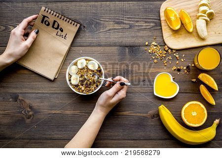 Good morning habits. Eat porridge and fruits and make to do list. Dark wooden background top view.