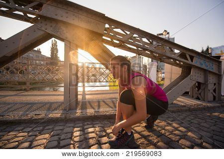 woman tying running shoes laces getting ready to run on city at sunny morning