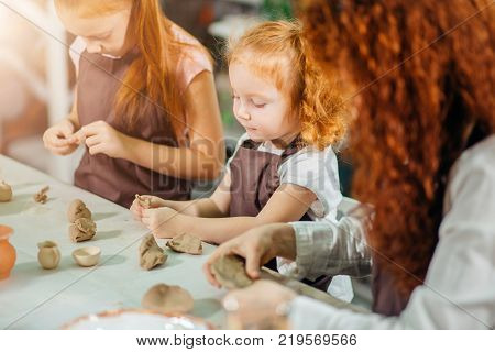 redhad Mother and two kid daughter at home molded from clay and play together