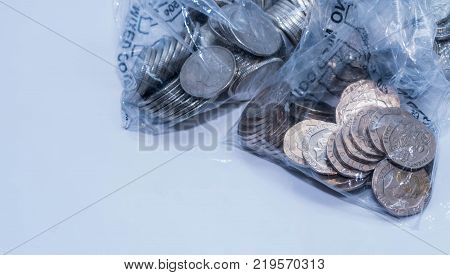 British coins in bank coing collecting plastic bags on a white background