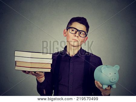 Student loan concept. Young man with stack pile of books and piggy bank full of debt rethinking future career path