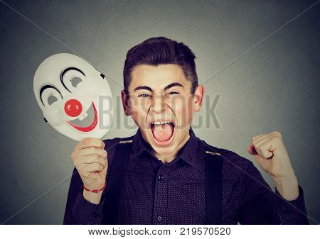 Portrait upset angry screaming man holding clown mask expressing cheerfulness happiness isolated on gray wall background. Human emotions feelings