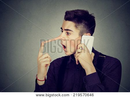 Surprised young man with long nose talking on mobile phone isolated on gray wall background. Liar concept. Human emotion feelings character traits