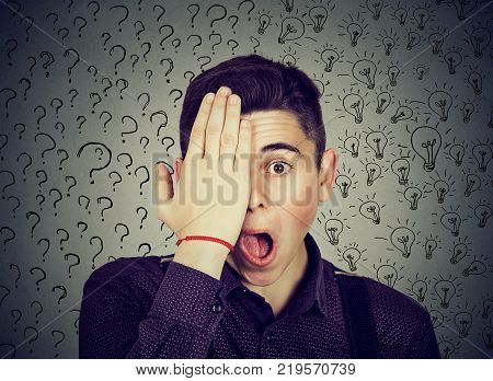 Young surprised man with many questions and answers idea light bulbs covering half of his face with hand