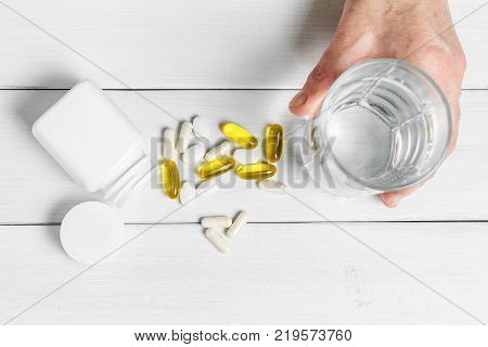 Woman hands takes yellow capsules of omega 3 white pills of calcium glucosamine supplements glass of water and plastic bottle on wooden planks table.