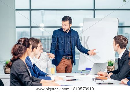 Director of company having business meeting with his staff. showing presentation on flipchart or magnetic desk