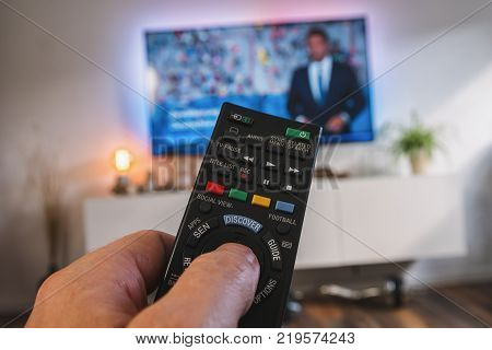 POV-Shot from a young man holding a TV Remote control to chance the tv channel on 4k TV at home. ideal for websites and magazines layouts