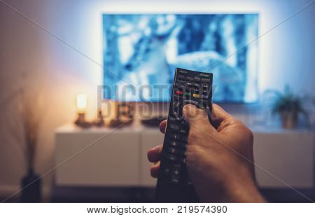 Pov shot from a young man watching a movie at home on a tv with a TV Remote control in his hand. ideal for websites and magazines layouts