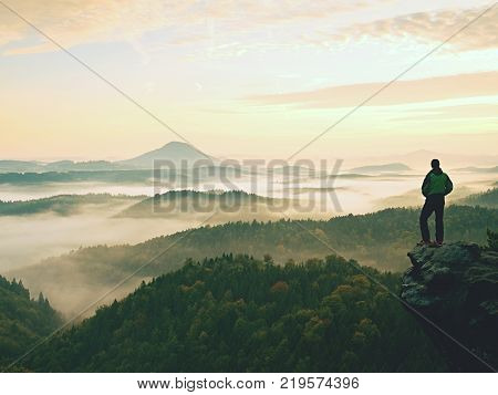 Hiker is standing on sandstone peak in rocky park and watching over misty and foggy morning valley to Sun. Beautiful moment miracle of nature. Hiker silhouette watching. Person standing