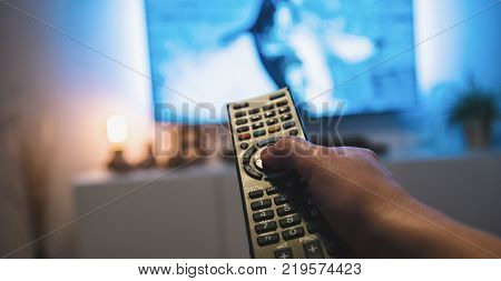 Pov shot from a young man watching tv at home with a TV Remote control in his hand. ideal for websites and magazines layouts