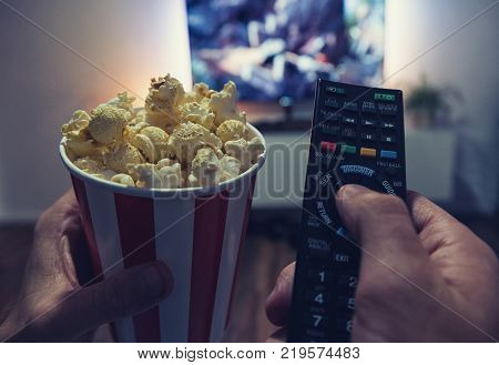 Pov shot from a young man watching a movie on a smarthome tv at home with popcorn box and TV Remote control in his hands. ideal for websites and magazines layouts