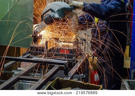 Cutting of metal parts using electric circular grinder in metalwork factory. Sparks while grinding.