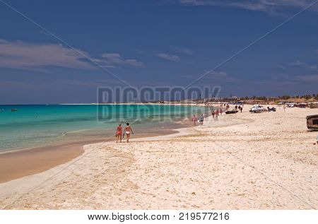 Vacationers strolling on the beautiful sandy beach on the island Sal, Cape Verde