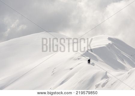 A man with his snowboard sitting on the snowy ridge of a mountain peak
