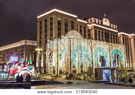 MOSCOW, RUSSIA - DECEMBER, 2017: Night Moscow during Christmas time in winter. The Christmas decorations near Manezh square and Tverskaya street against Duma.